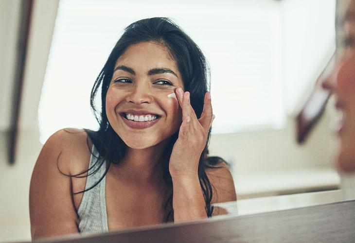 Ota haltuusi oikea ihonhoitorutiini. Nainen levittää ihollensa kasvovoidetta.