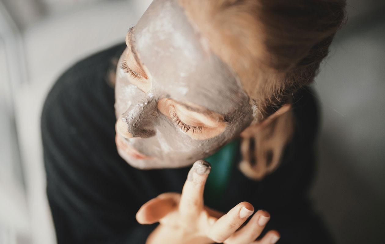 Savi on loistava ihonhoitorutiini. Nainen levittää kasvoilleen savinaamiota.