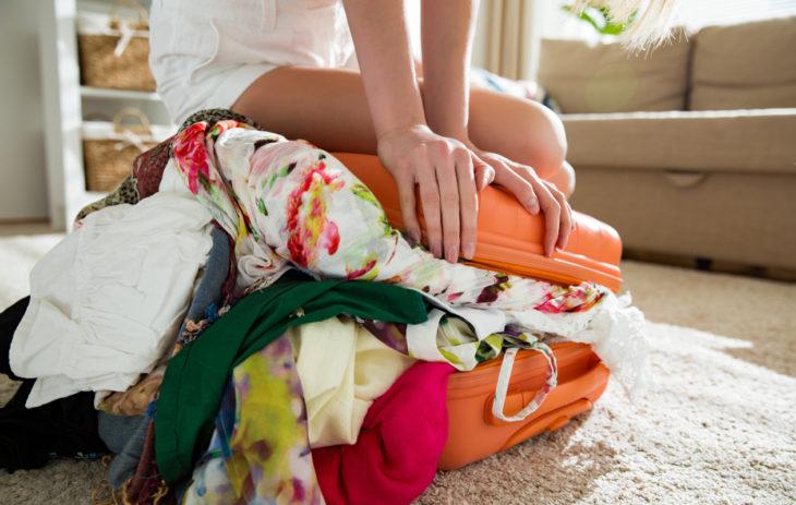 Nainen istuu yli pursuavan matkalaukun päällä.