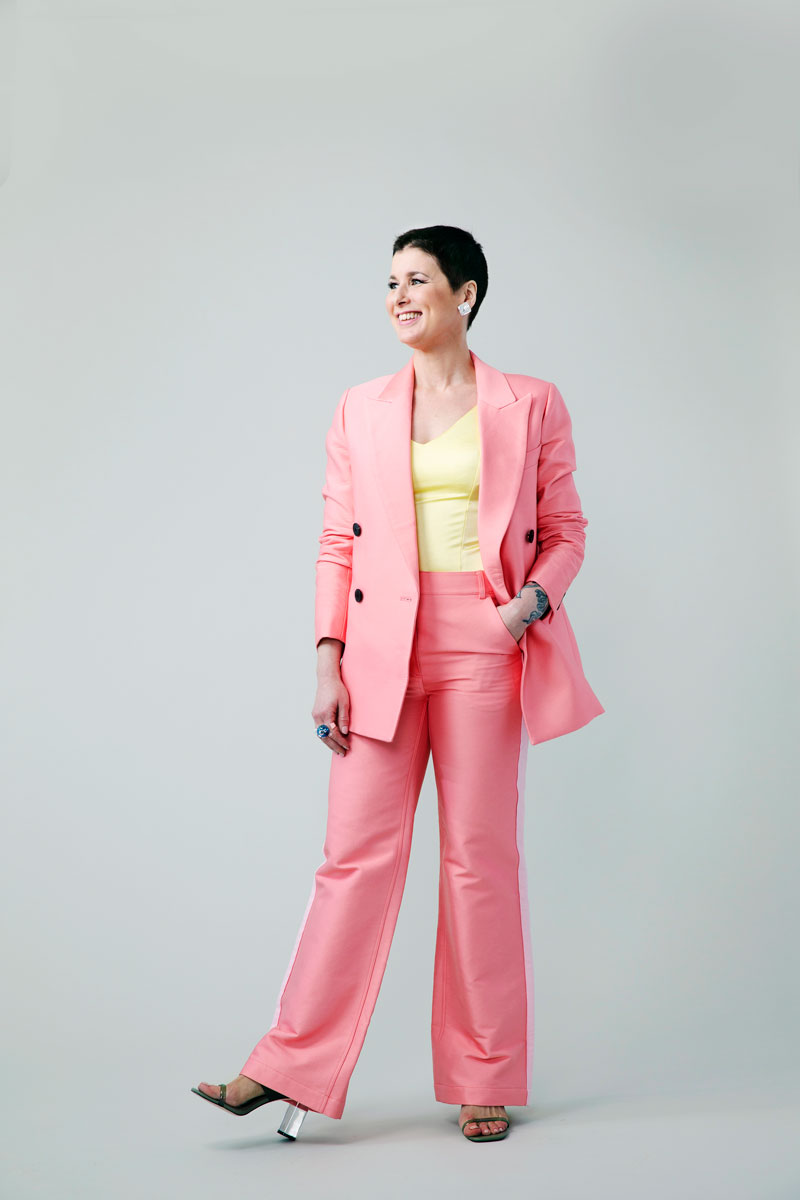 Hanna vaaleanpunaisessa housupuvussa.Jakkupukukammoiselle Hannalle näytettiin, että housupuvun voi asustaa myös erittäin nuorekkaasti ja hauskasti