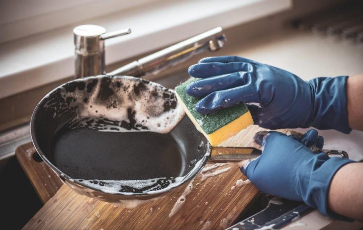 Nainen pesee teflonpannua.