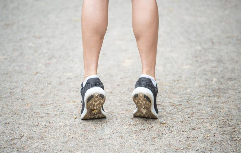 Nainen lämmittelee ennen juoksulenkkiä.