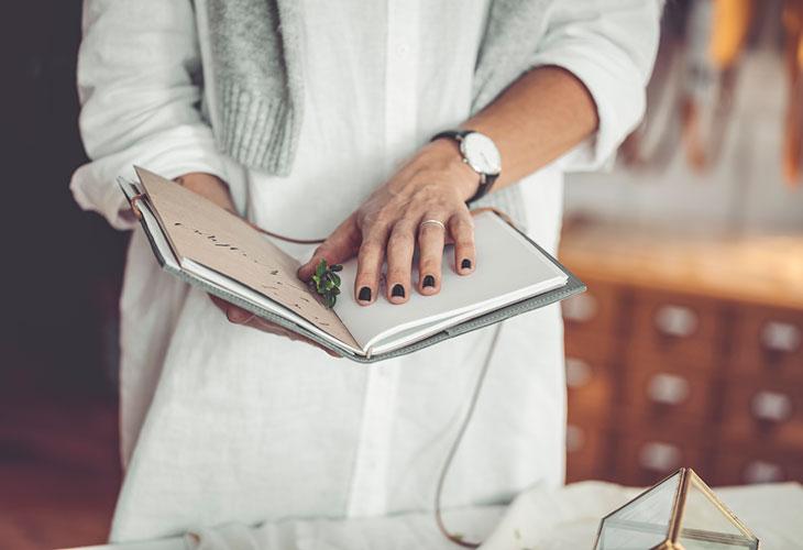Nainen kalenteri kädessä.