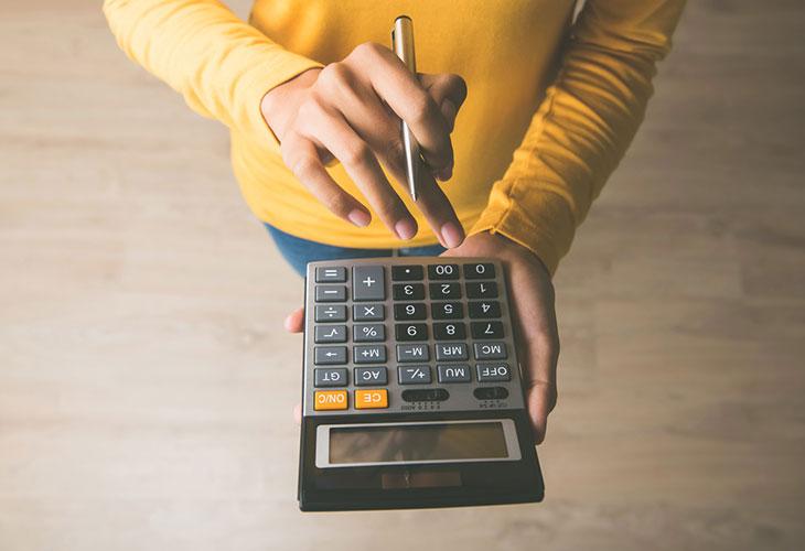 Nainen laskee asumiskuluja laskimella.