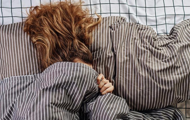 Nainen hoitaa hiuksiaan yöllä.