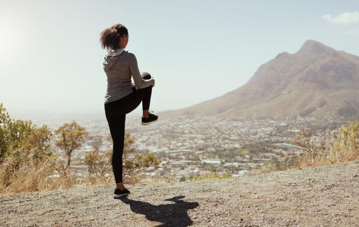 Nainen nostaa jalkaansa ja tukee jalkaa kädellä.