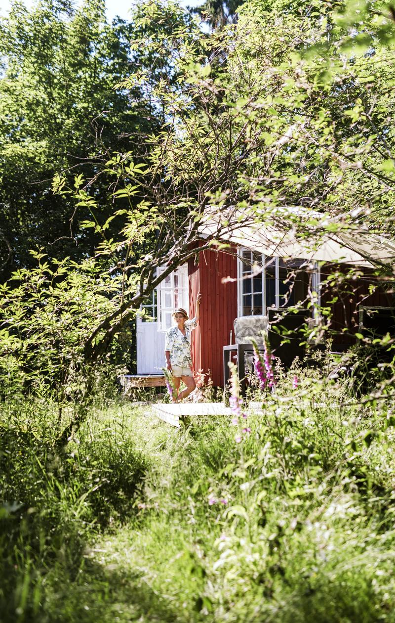 Pia Asikainen ja pieni punainen mökki kasvillisuuden seassa