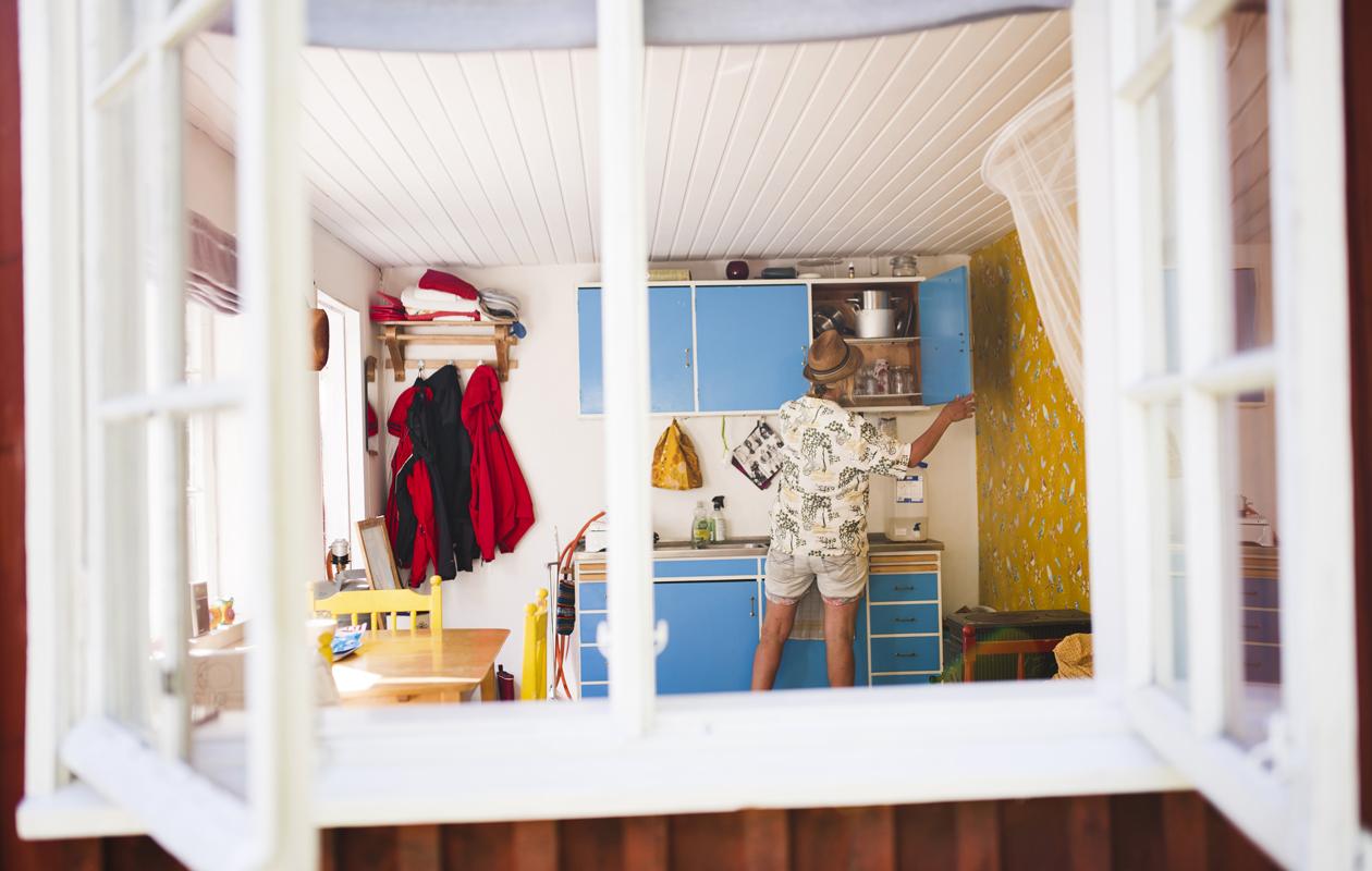 Pia Asikainen avaa keittiönkaapin sinisen oven
