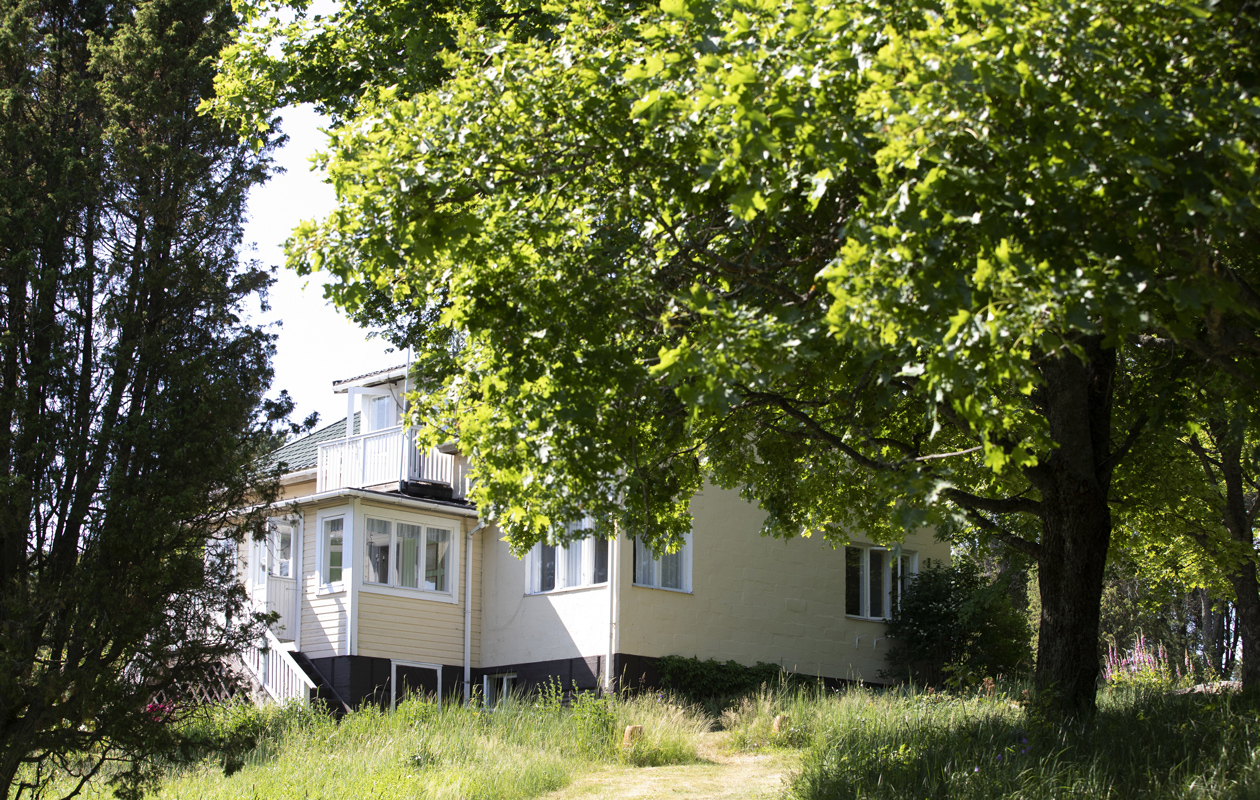 Keltainen suuri puutalo puiden siimeksessä