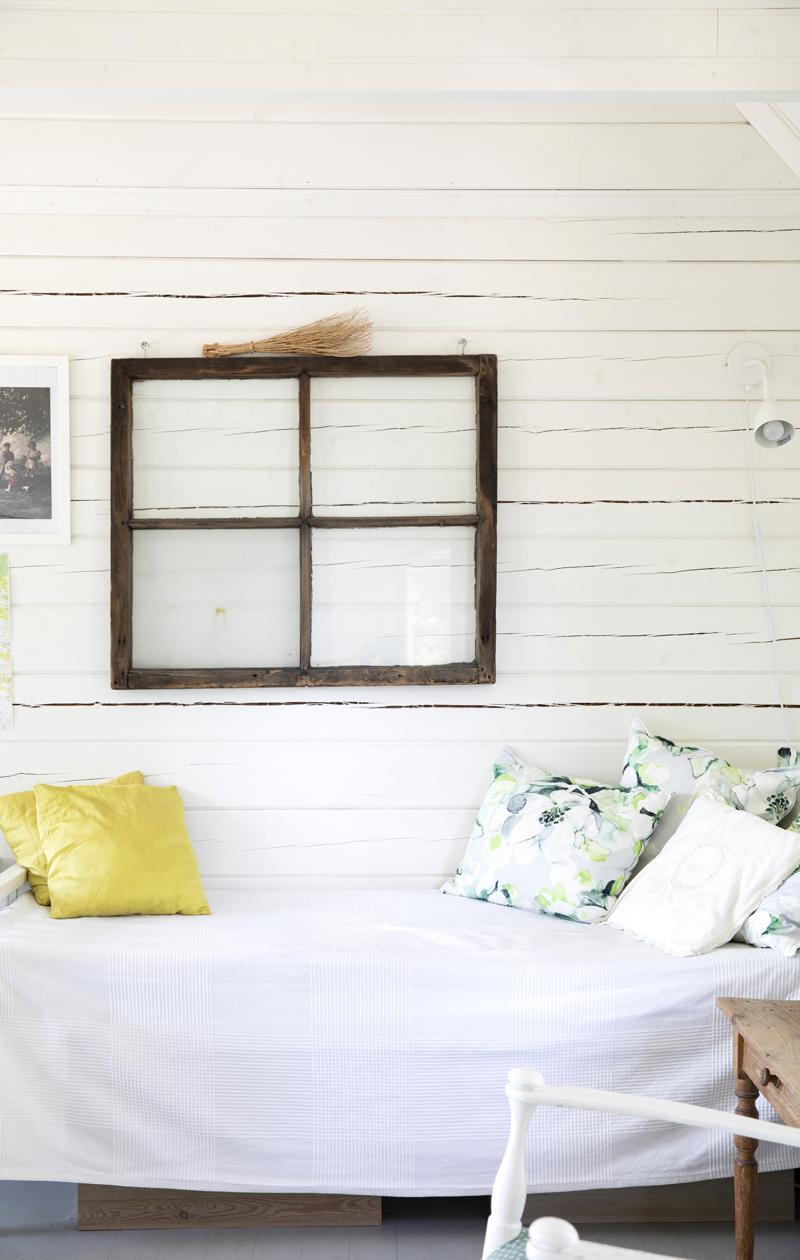 Vaaleasävyinen saunamökki ja sänky