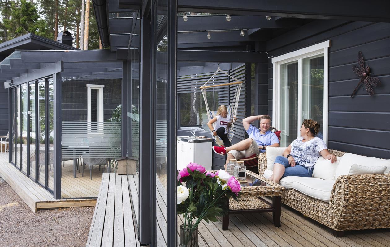 Aki Asikainen, vaimo Katja ja tytär Anita mökin terassilla