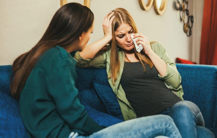 Kaksi naista istuu sohvalla ja toinen itkee.