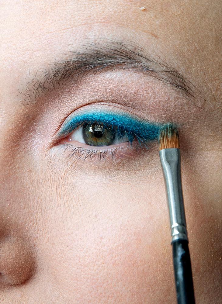 Värikäs meikki on trendikäs. Kuvassa malli lisää sinistä luomiväriä silmiin.
