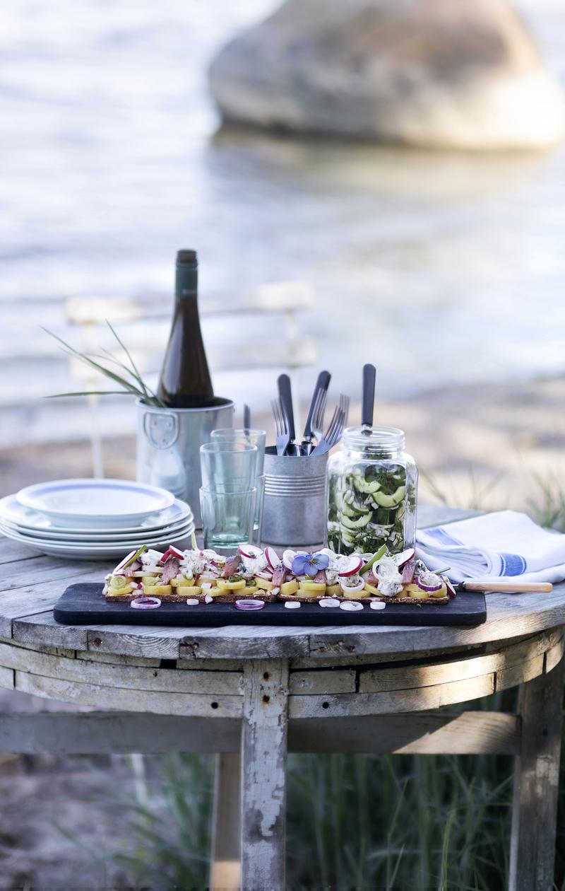 Sillileipä pöydällä rannalla.Sillileipä viimeistelläänisäämällä pinnalle kaprikset ja majoneesikastikenokareet.