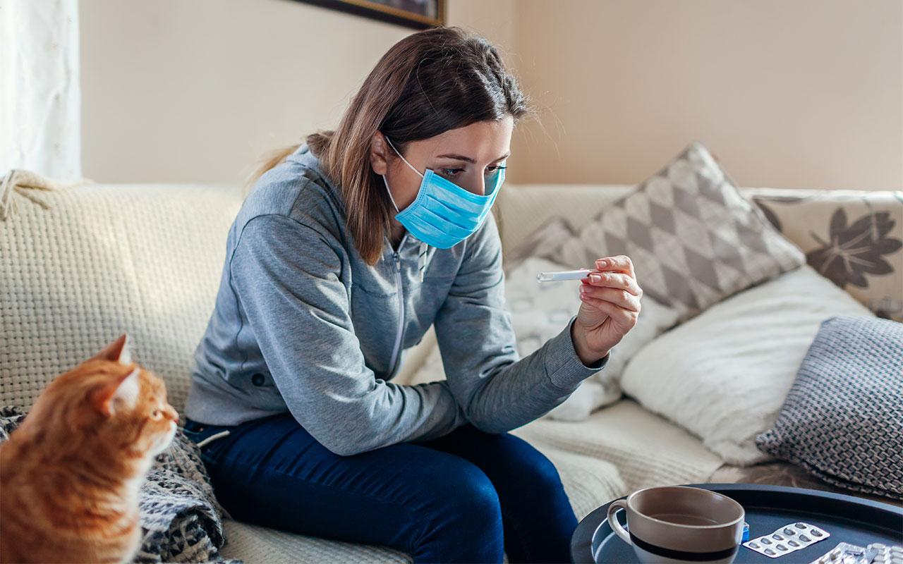 Nainen istuu sohvalla maski päässä. Koronaviruksen tarttuminen muihin voi pelottaa jopa enemmän kuin oma sairastuminen.