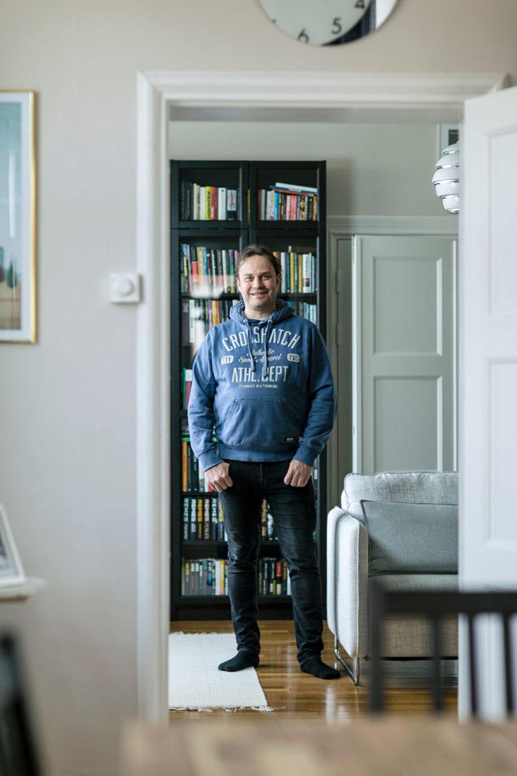 Harri Moisio seisoo kirjahyllyn edessä.
