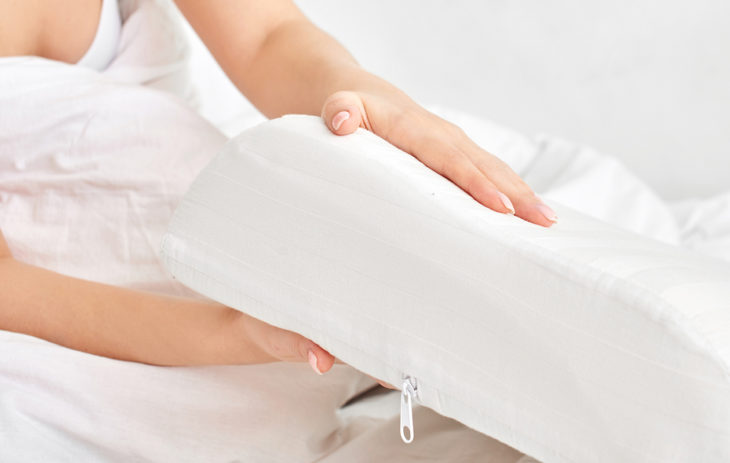 Nainen pitelee tyynyä. Hyvä nukkumisasento löytyy usein itsekseen.
