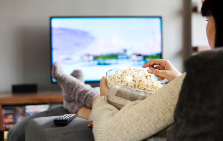 Hyvä istuma-asento on sellainen, joka ei kestä liian pitkään ajallisesti. Kuvassa nainen syö popcorneja ja pitää jalkoja ristissä nilkkojen kohdalta.