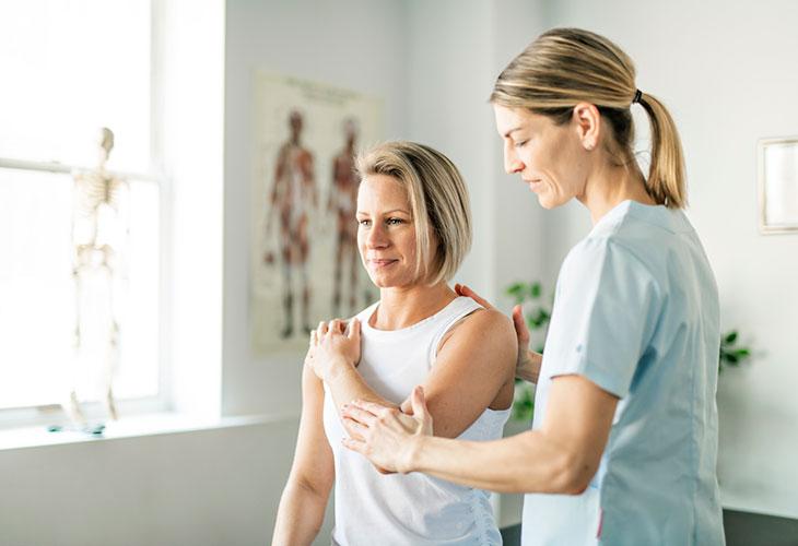 Emännän kyhmyyn liittyvää kipuilua voidaan hoitaa fysioterapeutilla. Kuvassa nainen fysioterapeutin vastaanotolla.