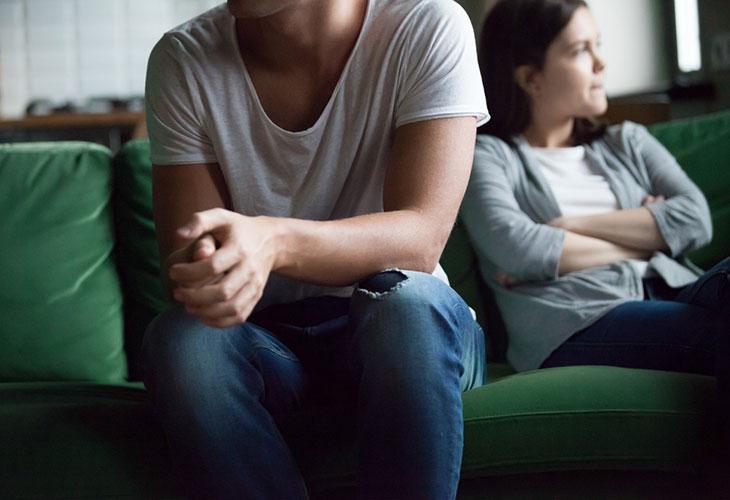 Itselle voi herätä kysymys siitä, miksi exä ottaa uudelleen yhteyttä. Kuvassa nainen ja mies sohvalla.