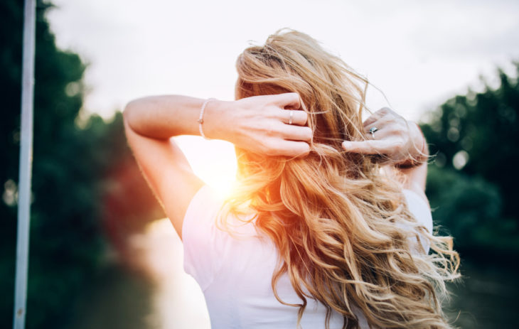 Energialeikkaus sopii hyvin pitkiä hiuksia kasvattavalle. Kuvassa nainen, jolla on pitkät, kiharat hiukset.