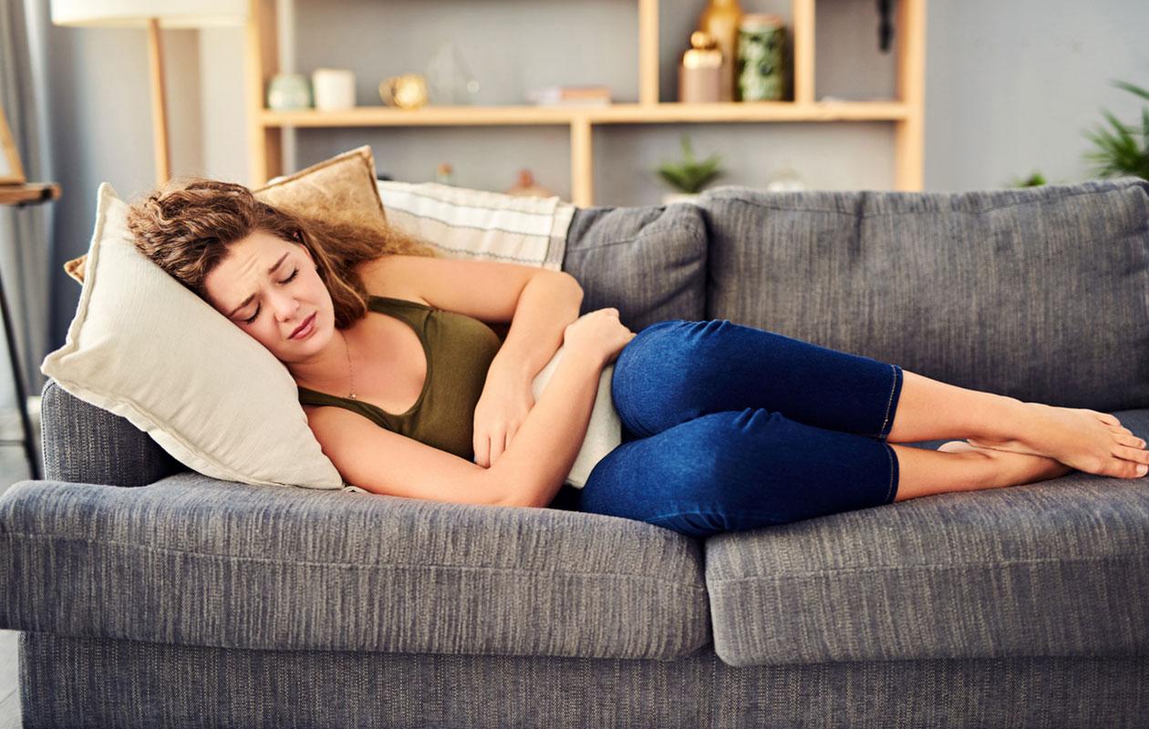 psykofyysinen fysioterapia, nainen makaa sohvalla kivuliaana.