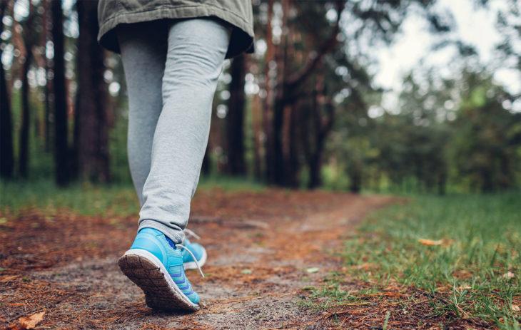 Nainen kävelee metsässä. Nivelrikko voi aiheuttaa ikäviä oireita ja kipuja, mutta nivelrikkoisenkin olisi tärkeää pysyä liikkeessä.