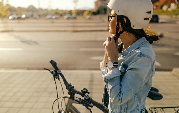 Nainen pyörän vieressä laittamassa kypärää kiinni. Pyöräilyn hyödyt riippuvat usein siitä, millaista matkaa polkee ja miten usein.