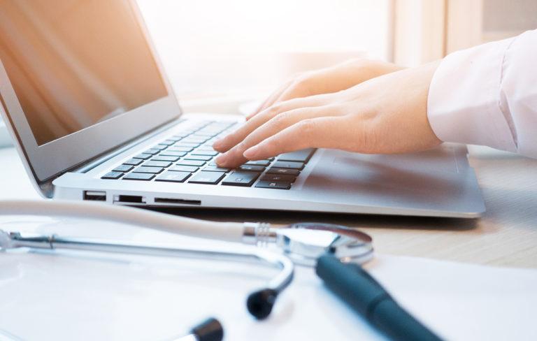 Lääkäri näppäilee tietokonetta.