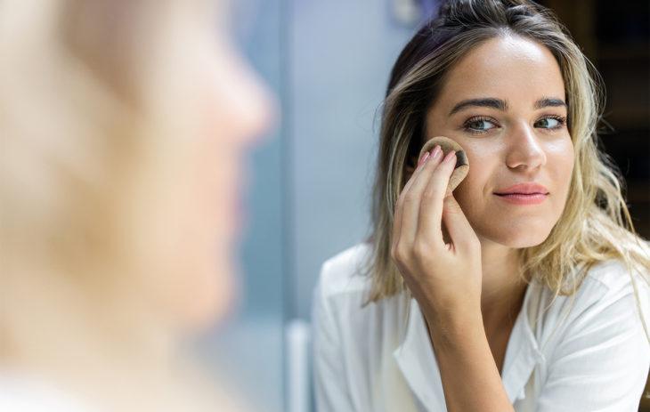 Nainen puuteroimassa kasvoja. Itseruskettava kasvoille on helppo levittää, jos on tehnyt ihon pohjatyöt hyvin-