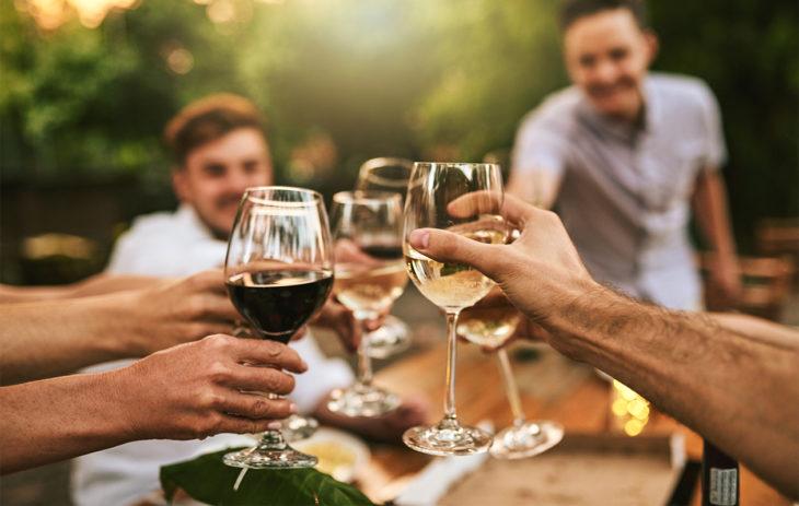 Kuva ihmisistä juomassa viiniä. Ihmisillä voi olla hyvinkin erilaiset päihdearvot, myös parisuhteessa.