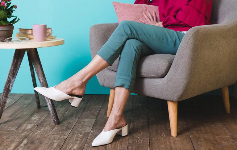 Nainen istuu jalka toisen päällä.