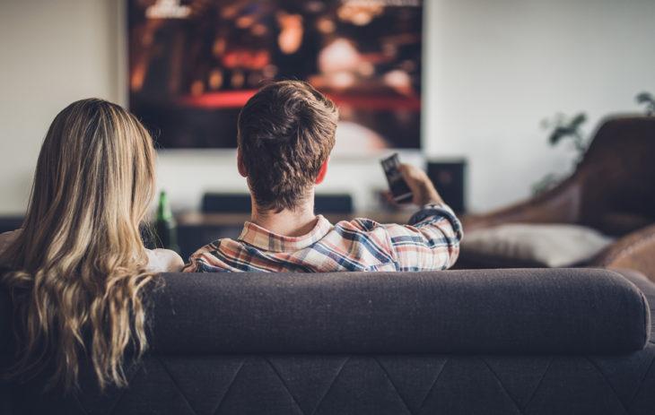 Nainen ja mies viettävät leffailtaa kotona. Jalka toisen päällä istuminen tai mikä tahansa muu pitkään staattisena pysyvä asento, ei ole suositeltavaa.