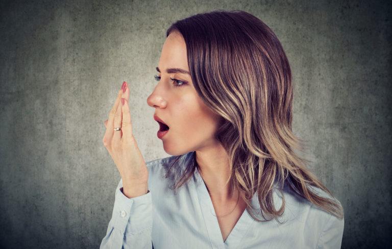 halitoosi, nainen tarkistaa hengitystään.