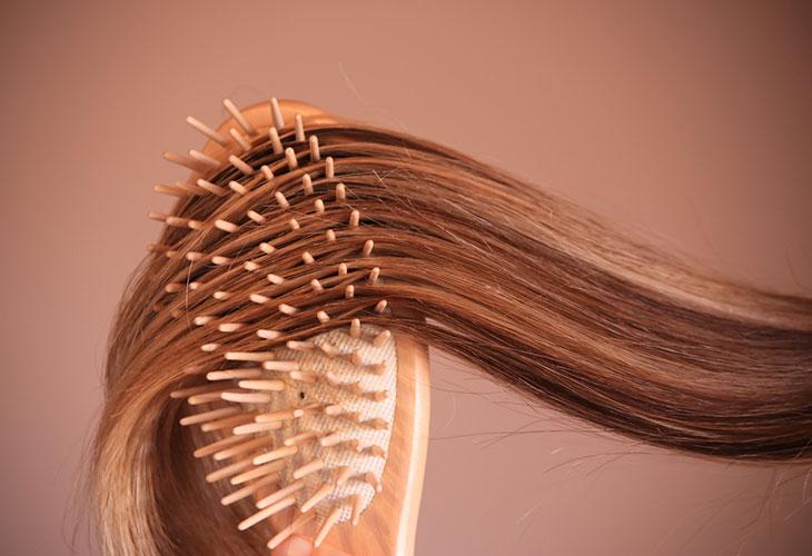 Hiusharjan pesu kannattaa tehdä säännöllisesti. Kuvassa henkilö harjaa hiuksia.