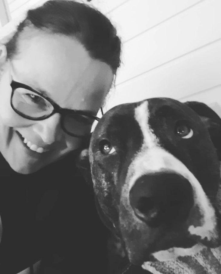 Selfiessä Riikka Sundberg hymyilemässä Jefe-koiran vieressä.