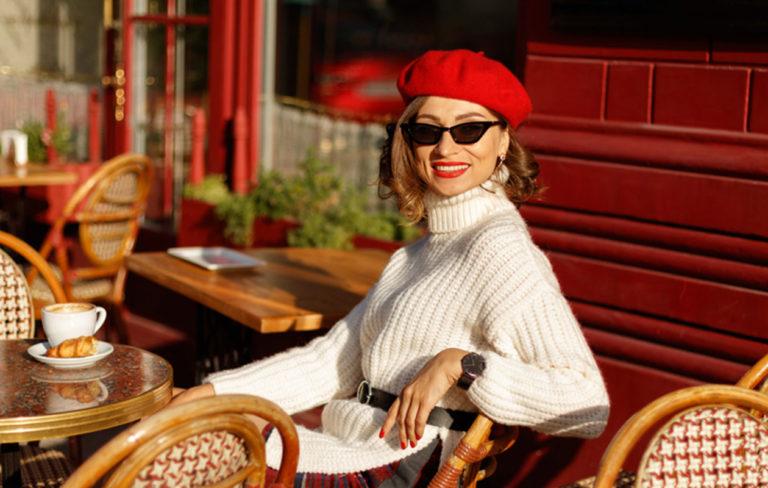 Lyhyet hiukset 2020 inspiroituvat Pariisista. Kuvassa nainen ranskalaisessa kahvilassa.