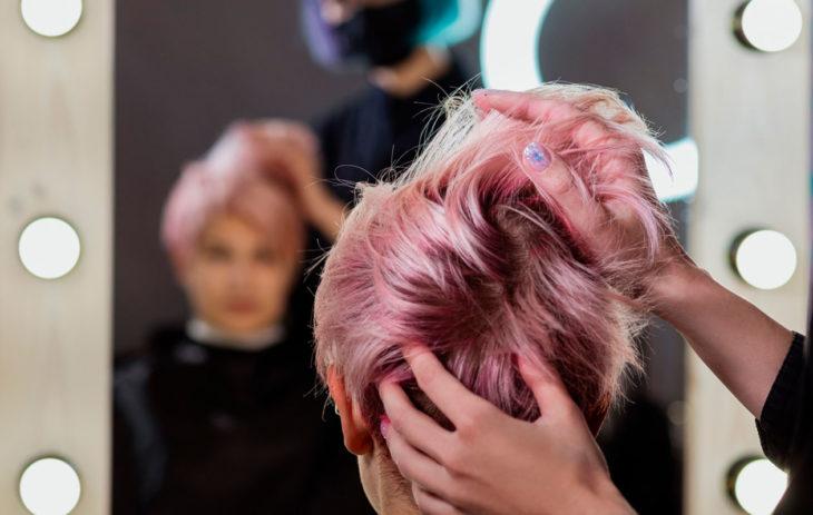 Värikkäät sävyt kuuluvat syksyn 2020 hiusväreihin. Kuvassa nainen kampaajalla.