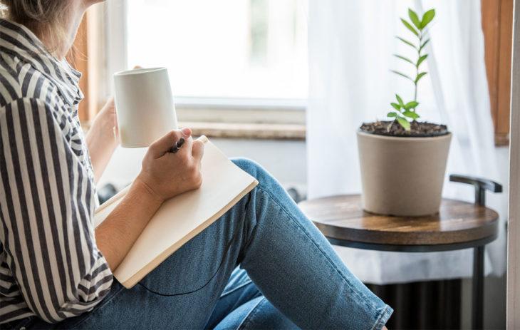 Nainen istuu kuppi kädessä kirjoittamassa päiväkirjaa. Tunteet kuuluvat jokaisen ihmisen elämään, mutta niitä voi oppia myös käsittelemään.