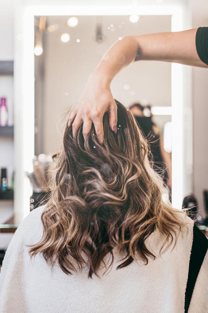 Digitaalinen permanentti luo hiuksiin luonnollista taipuisuutta. Kuvassa nainen kampaajalla.
