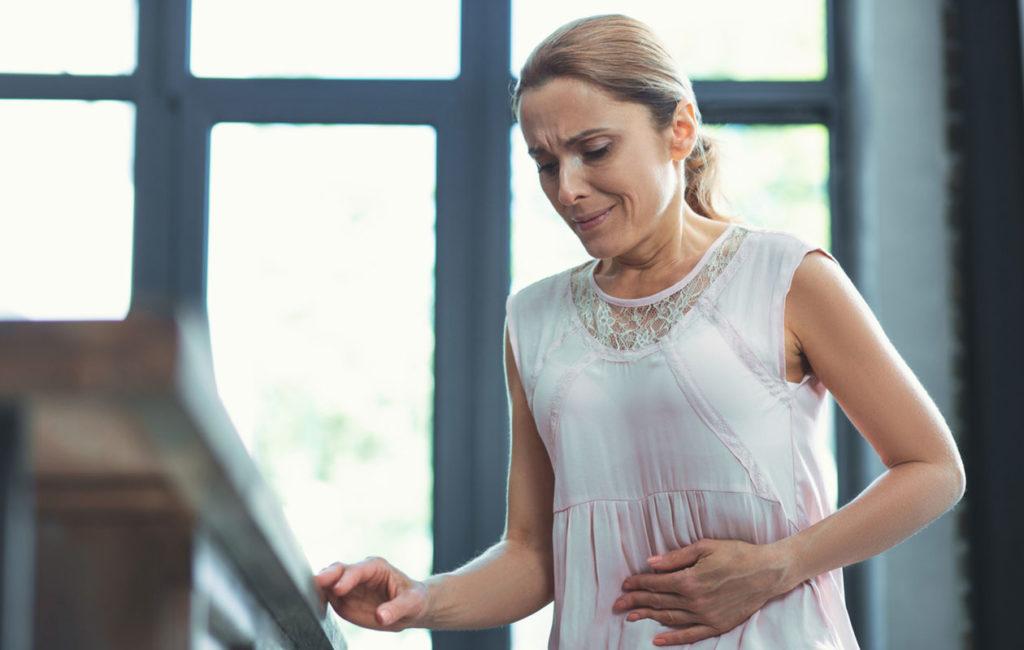Matalat mahahapot aiheuttavat turvotusta. Kuvassa nainen pitelee vatsaansa.