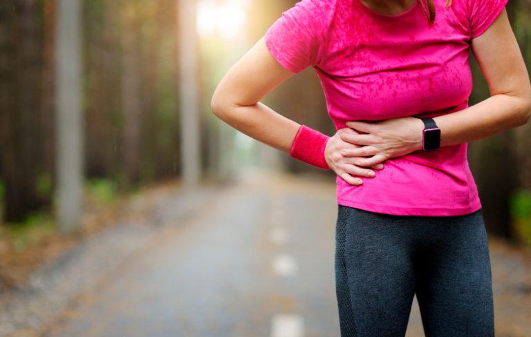 Pistävä kylkikipu on liikunnan aikana vaaraton vaiva. Kuvassa nainen pitelee kylkeä juoksulenkillä.