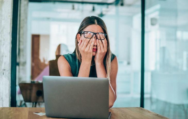 Omaehtoinen luottikielto, stressaantunut nainen tietokoneella.