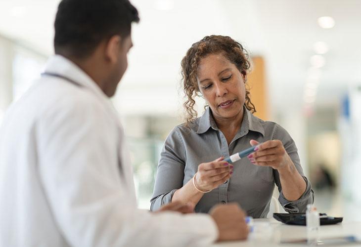 Tyypin 1 diabetes voi puhjeta myös aikuisella iällä. Kuvassa nainen lääkärin vastaanotolla insuliinikynä kädessä.