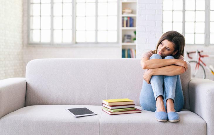 Nainen istuu sohvalla ja halaa polvia. Alemmuuskompleksi voi aiheuttaa muun muassa uupumista.