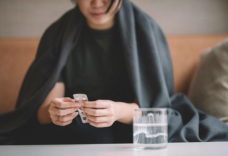 Ibuprofeeni vai parasetamoli? Kipulääkkeitä voi lääkärin mukaan syödä tarvittaessa yhdessä. Kuvassa nainen istuu sohvalla lääkepakkaus kädessään.