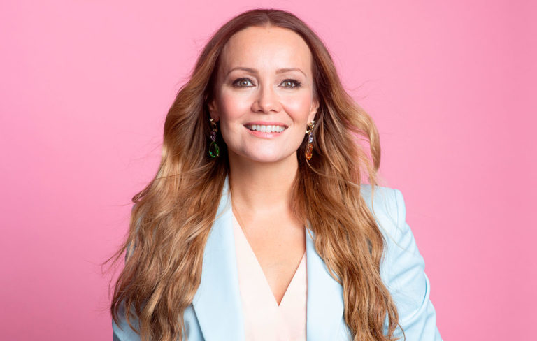 Marja Hintikka hymyilee sinisessä jakkupuvussa.