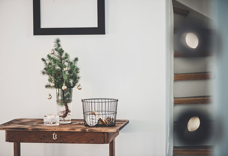 Kuivakukat tuovat kotiin tunnelmaa, kuten myös pienet havupuut. Kuvassa havupuum joka on asetettu pöydälle lasimaljakkoon.