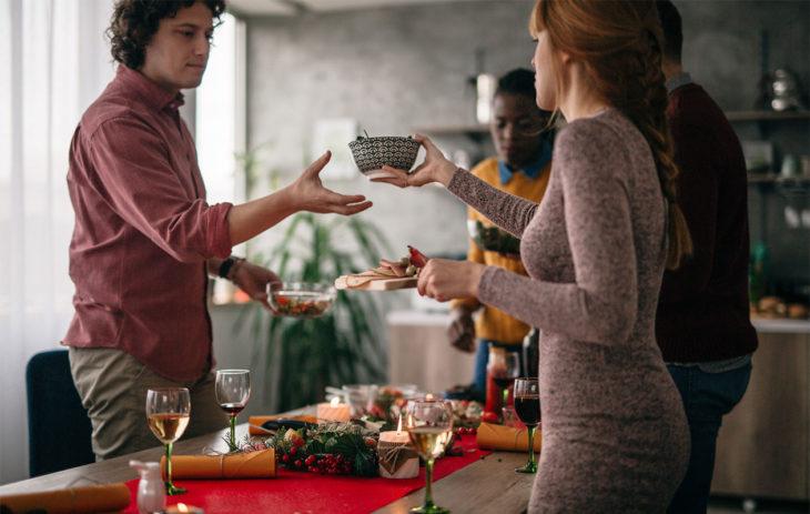 Ihmisiä pöydän ääressä aloittamassa ruokailua. Maailman parhaat siivousohjeet jouluun ovat: ilman joulusiivoustakin pärjää.