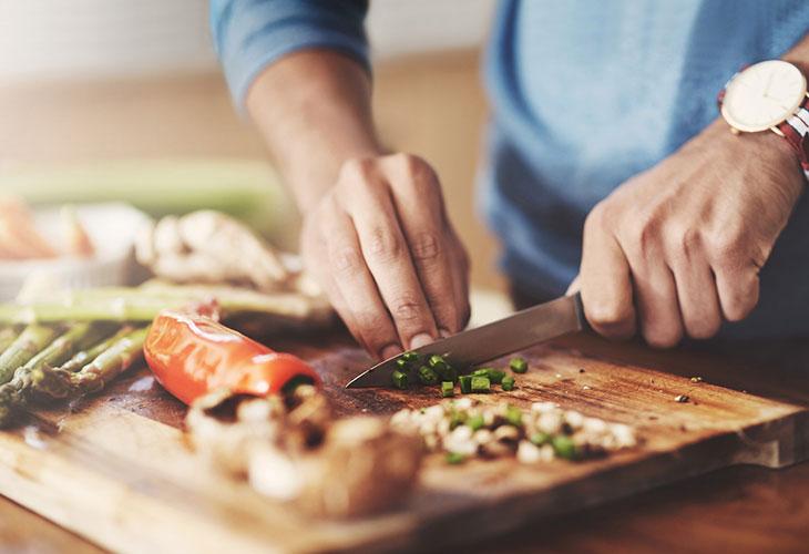 Ruoanlaittajan joululahjaideat voivat olla esimerkiksi laadukas veitsisetti. Kuvassa henkilö leikkaa veitsellä kasviksia.